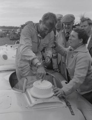 Stirling Moss qui fêtait ses 26 ans la veille de la course (17 octobre) déguste un appétissant gâteau préparé par sa Môman Source : Collection George Phillips