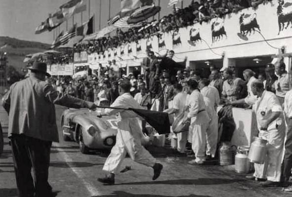 Arrêt au stand pour la n°104. Alfred Neubauer, directeur de course chez Mercedes, au premier plan, tenant le drapeau.